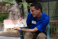 Corey reads the Ako Series to children at the zoo.